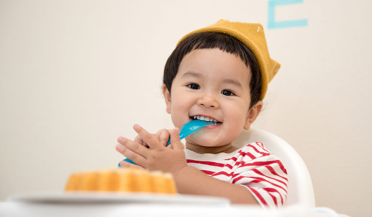 Young boy wearing a knitted yellow crown, sat in his chair eating cake.