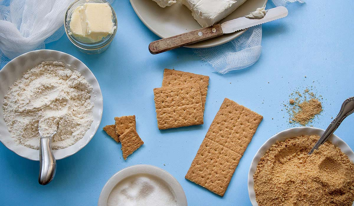 Baking ingredients: butter, flour, crumbled biscuits.