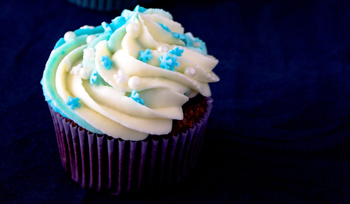 Chocolate cupcake with blue star sprinkles on the white frosting.