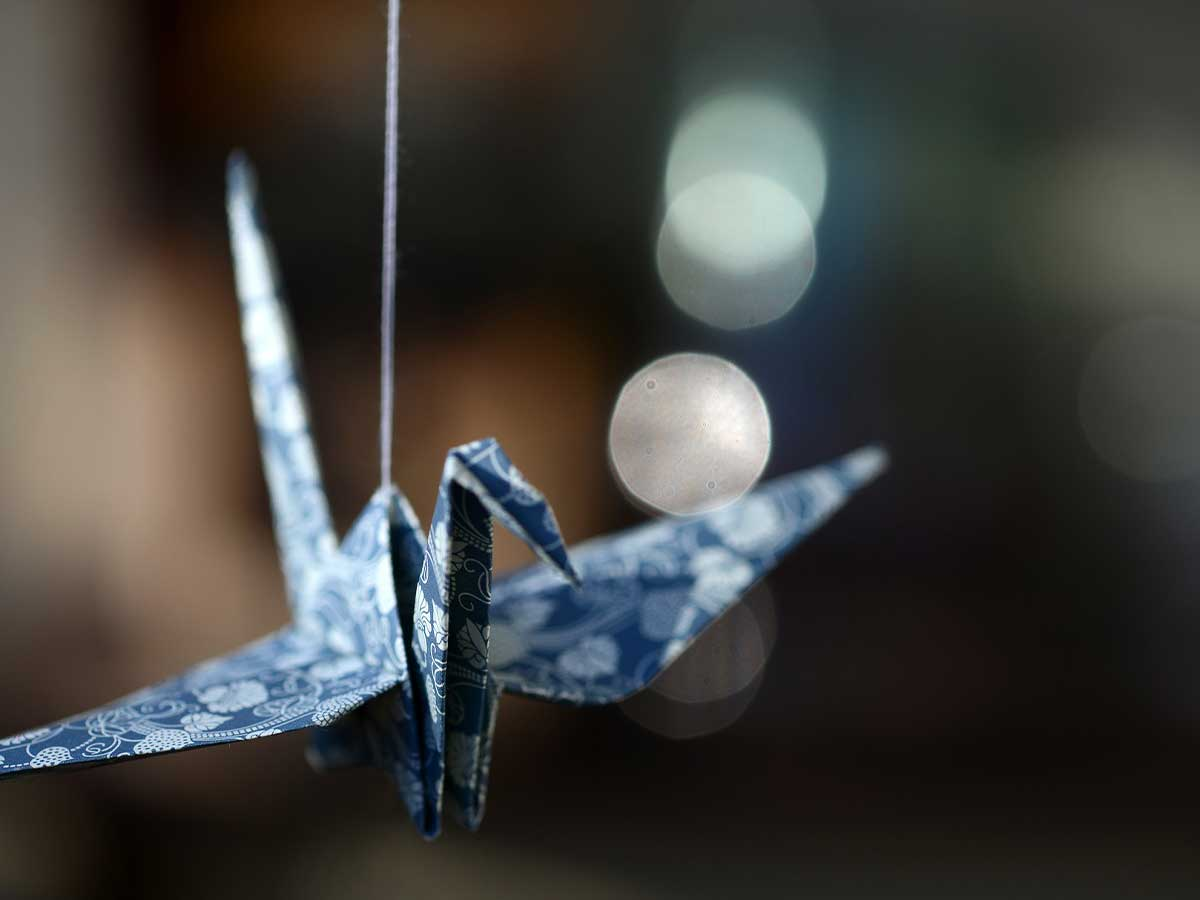 Blue patterned origami swan hanging from a string.
