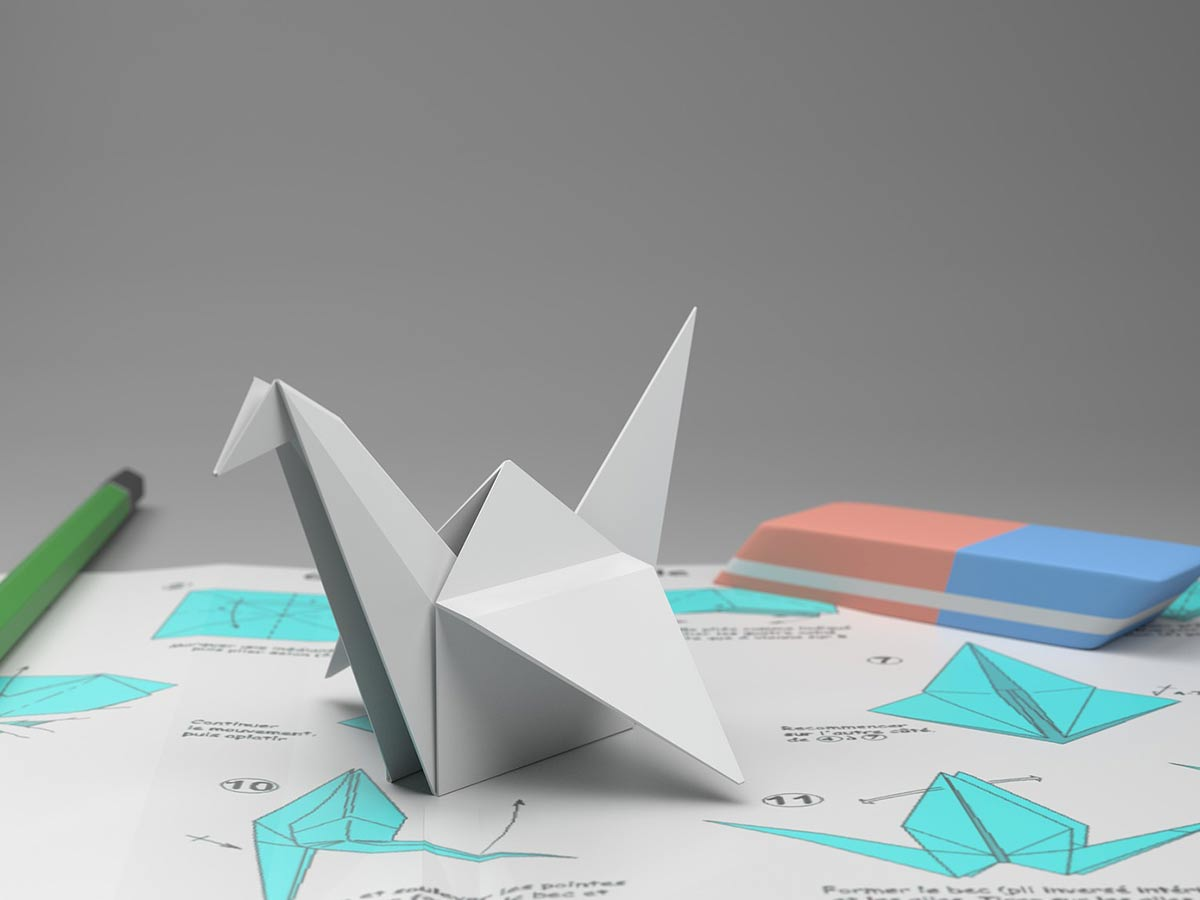White origami swan placed on top of the instructions for making an origami swan.