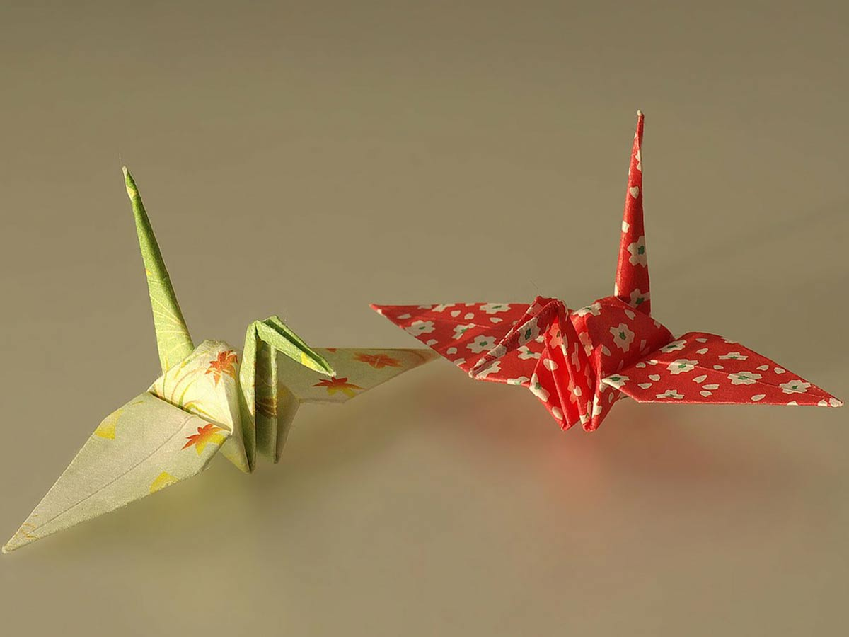 A yellow patterned origami swan and a red patterned origami swan.