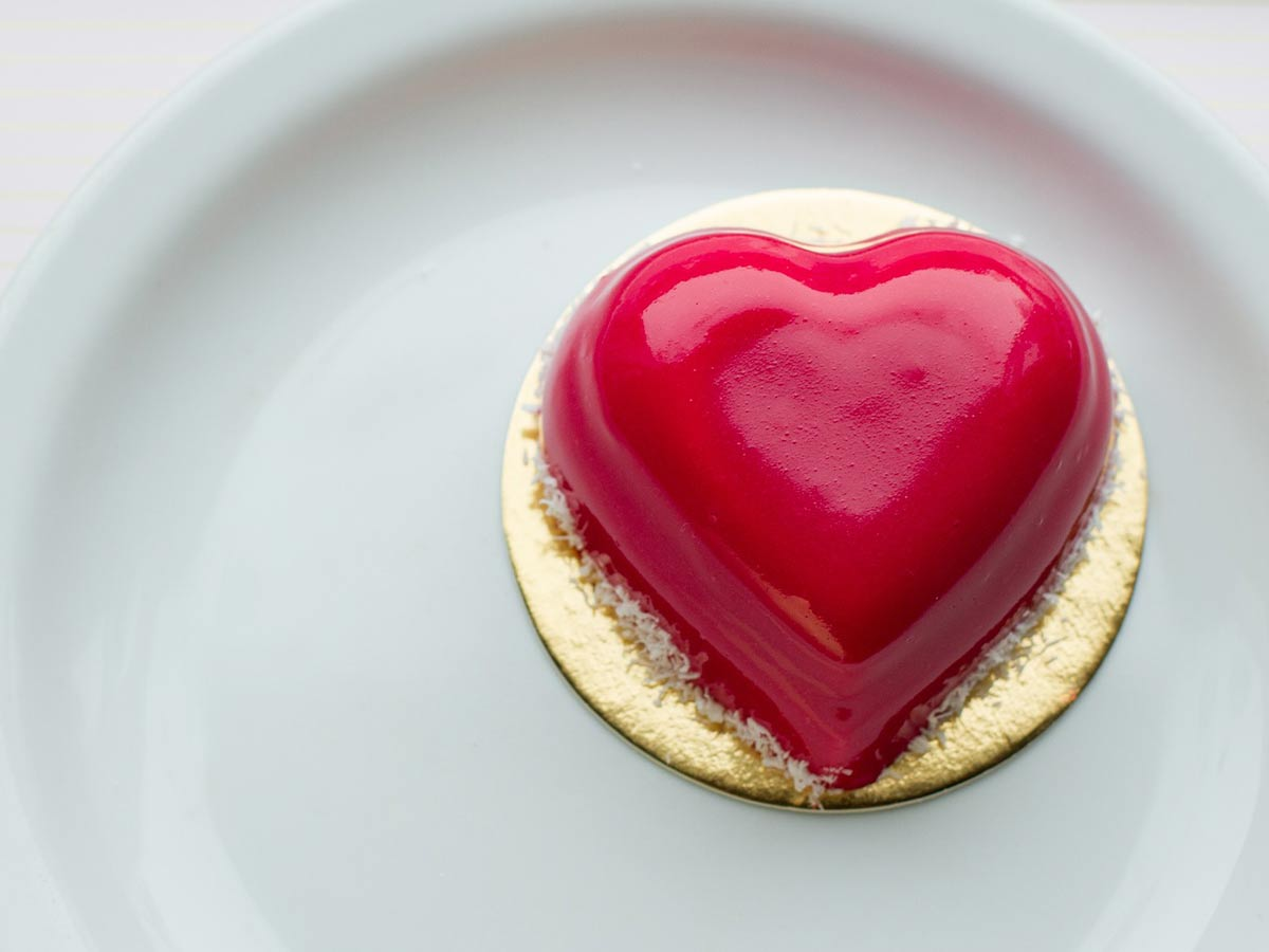 Small, individual-sized red, heart shaped cake on a plate.