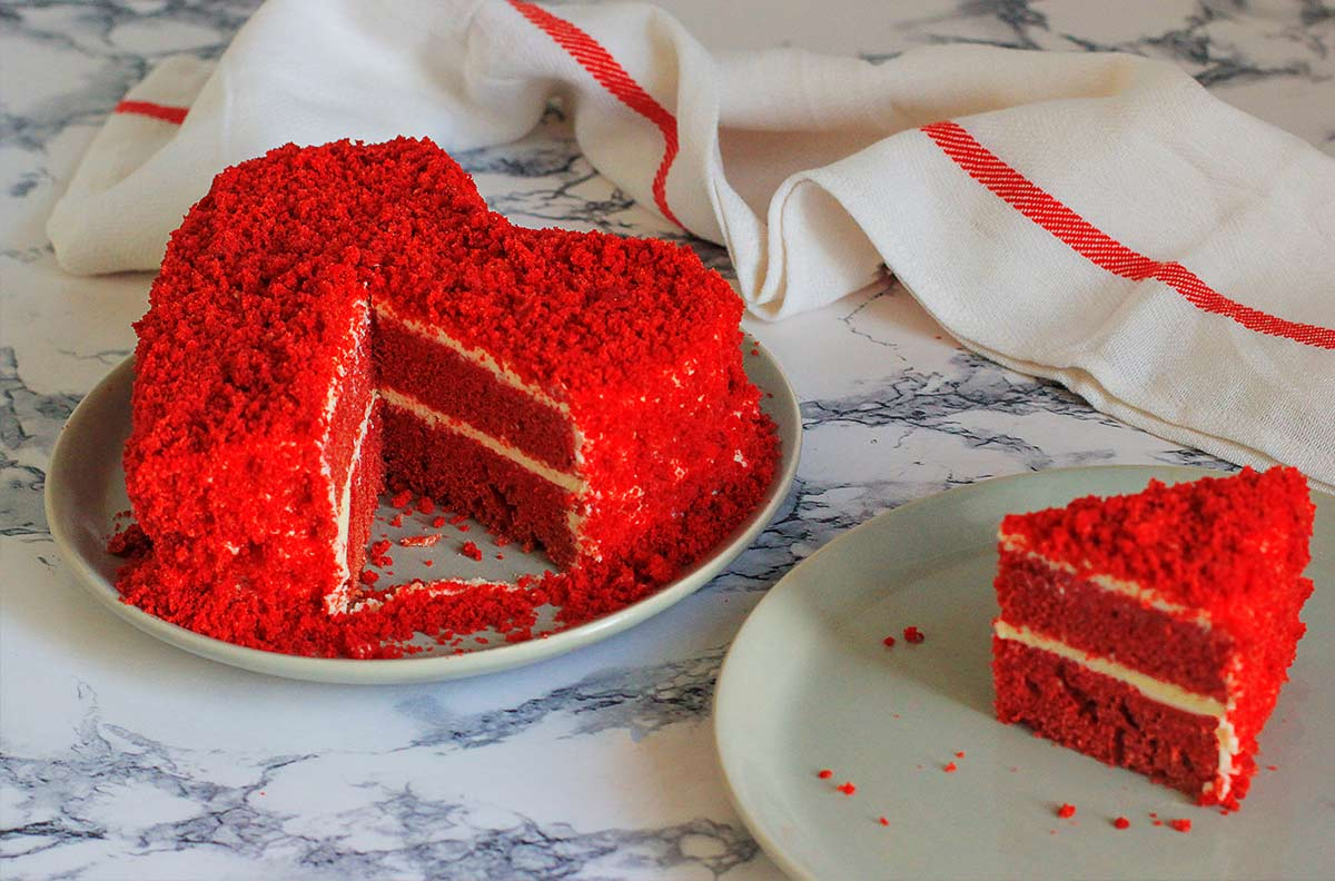 Red heart shaped red velvet cake with cake crumbled on top of the frosting.