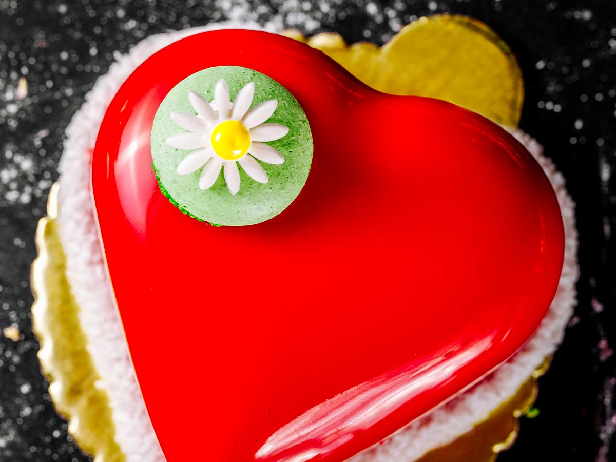 Red heart shaped cake with a green macaron with a daisy on top, on top of the cake.