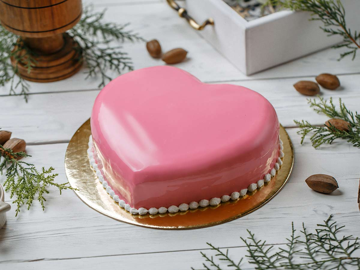 Pink heart shaped cake on a gold cake board.