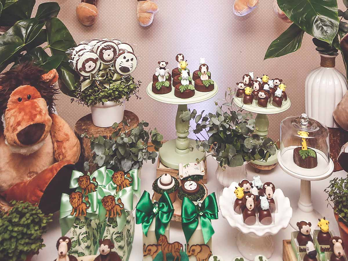 A whole table of jungle-themed cakes and sweet treats.