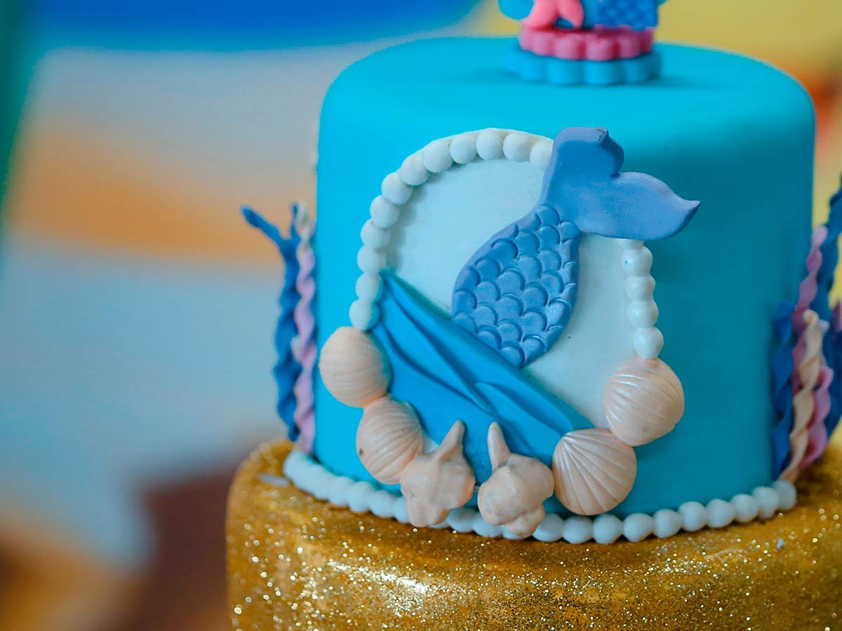 Under-water-themed cake with blue icing and a mermaid's tail on the side.
