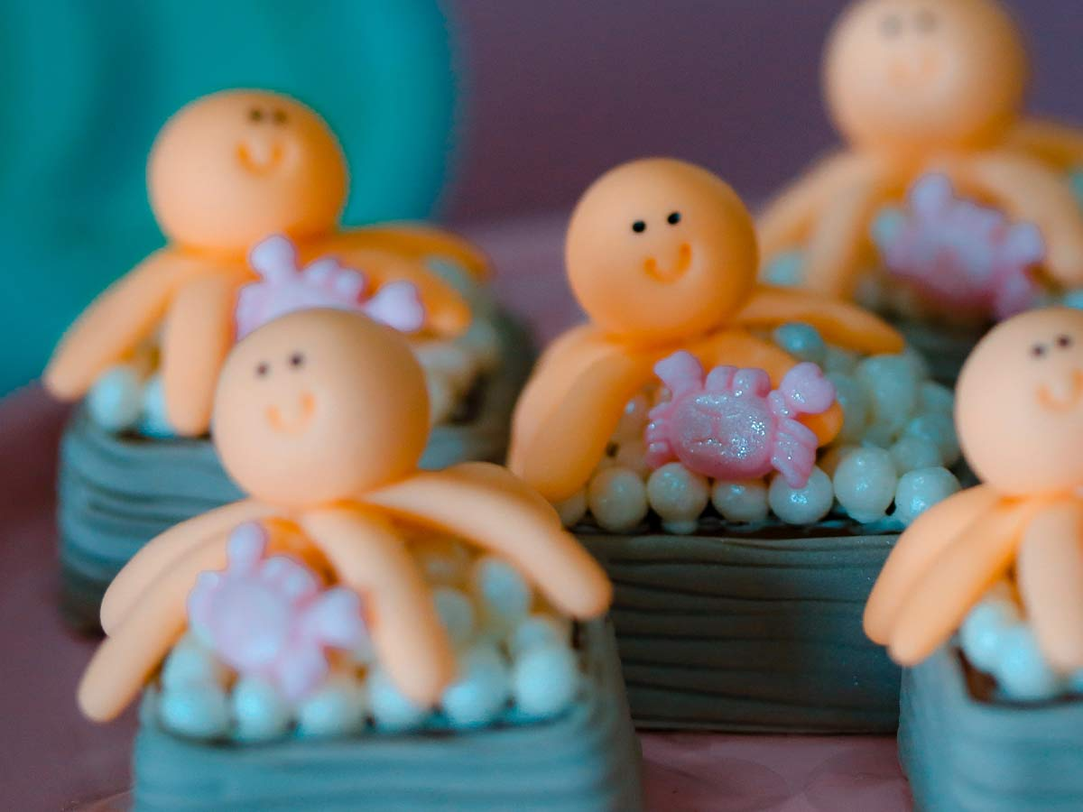 Little cakes decorated with squids made from icing on top.