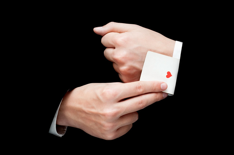 Someone pulling a card out of their black suit sleeve in a magic trick.