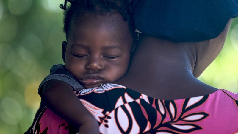 Baby girl sleeping on her mum's shoulder in her arms.