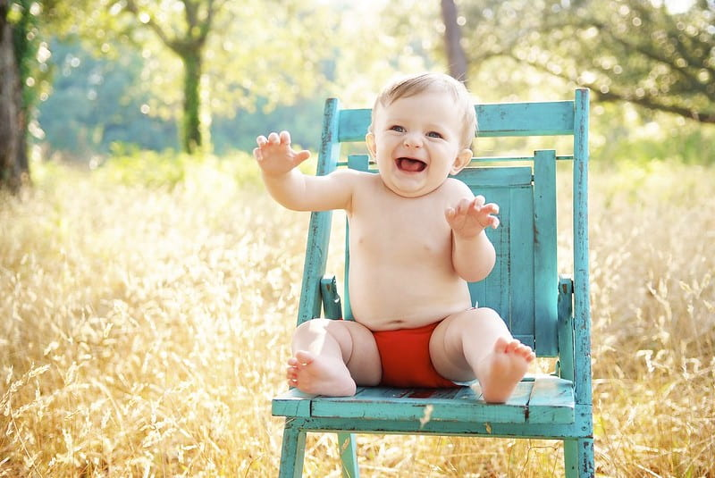 Baby boy sat on a blue garden chair outdoors, smiling and making silly faces.