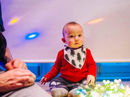 Small baby wearing a bib with Christmas trees on, sat on the floor looking at some Christmas lights.