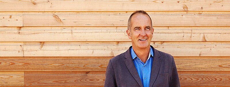 Designer Kevin McCloud standing in front of a wooden panelling smiling.