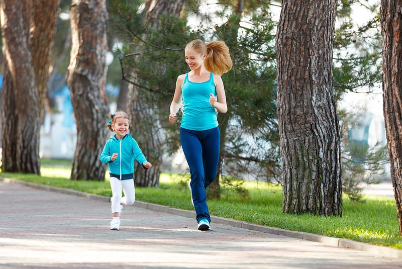 Mum and young daughter running together in the park.
