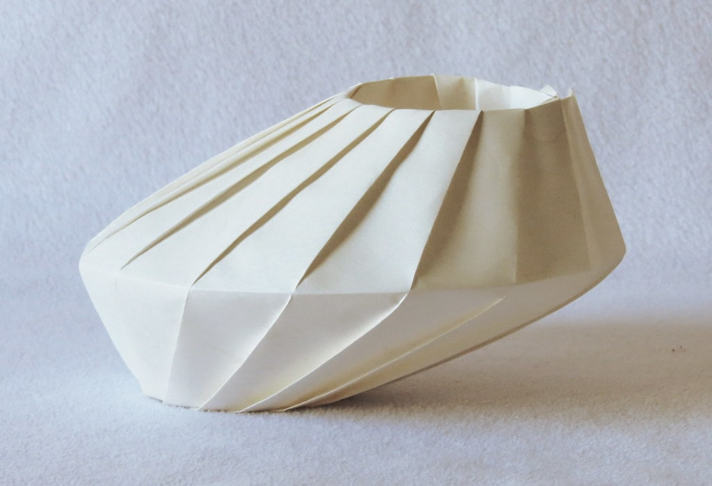 A white origami bowl placed on a white surface.