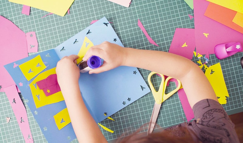 Little girl sat at a table making an origami birthday card, sticking on designs with glue.