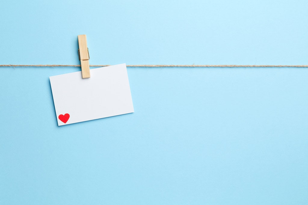 Piece of white card with a red heart in the bottom corner hanging from a string by a wooden peg.