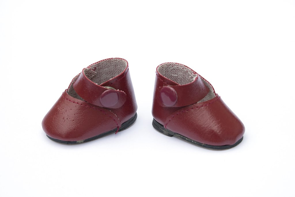 A pair of vintage baby doll's red leather shoes.