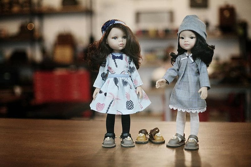 Two dolls wearing leather slip-on shoes, with a third pair on the floor between them.