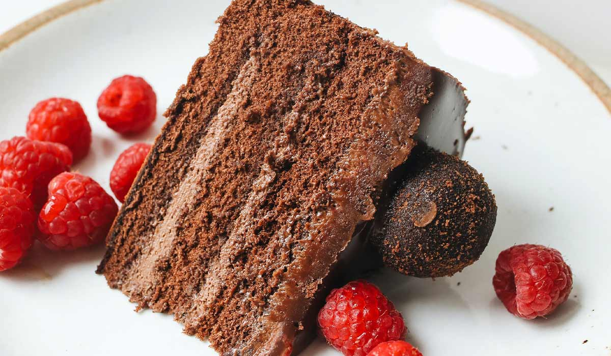 Slice of chocolate cake on a plate served with raspberries.