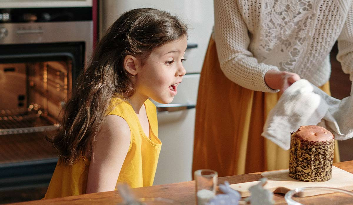 Little girl in the kitchen amazed at a chocolate cake her mum is taking out the oven.