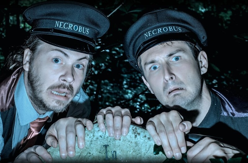 Two actor tour guides in conductor hats looking terrified into a light.