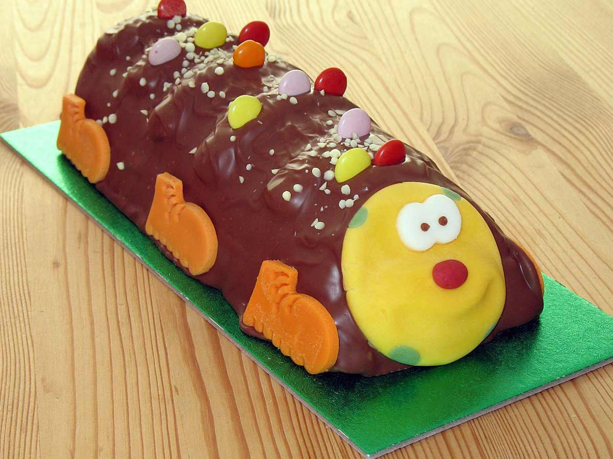 Chocolate caterpillar birthday cake on a green cake board.