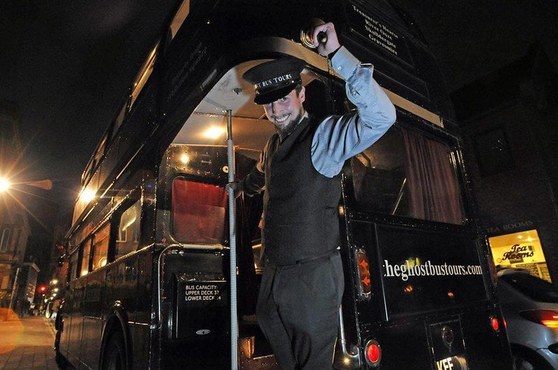 An actor guide tipping his hat at the camera at the entrance to the Ghost Bus Tour York.
