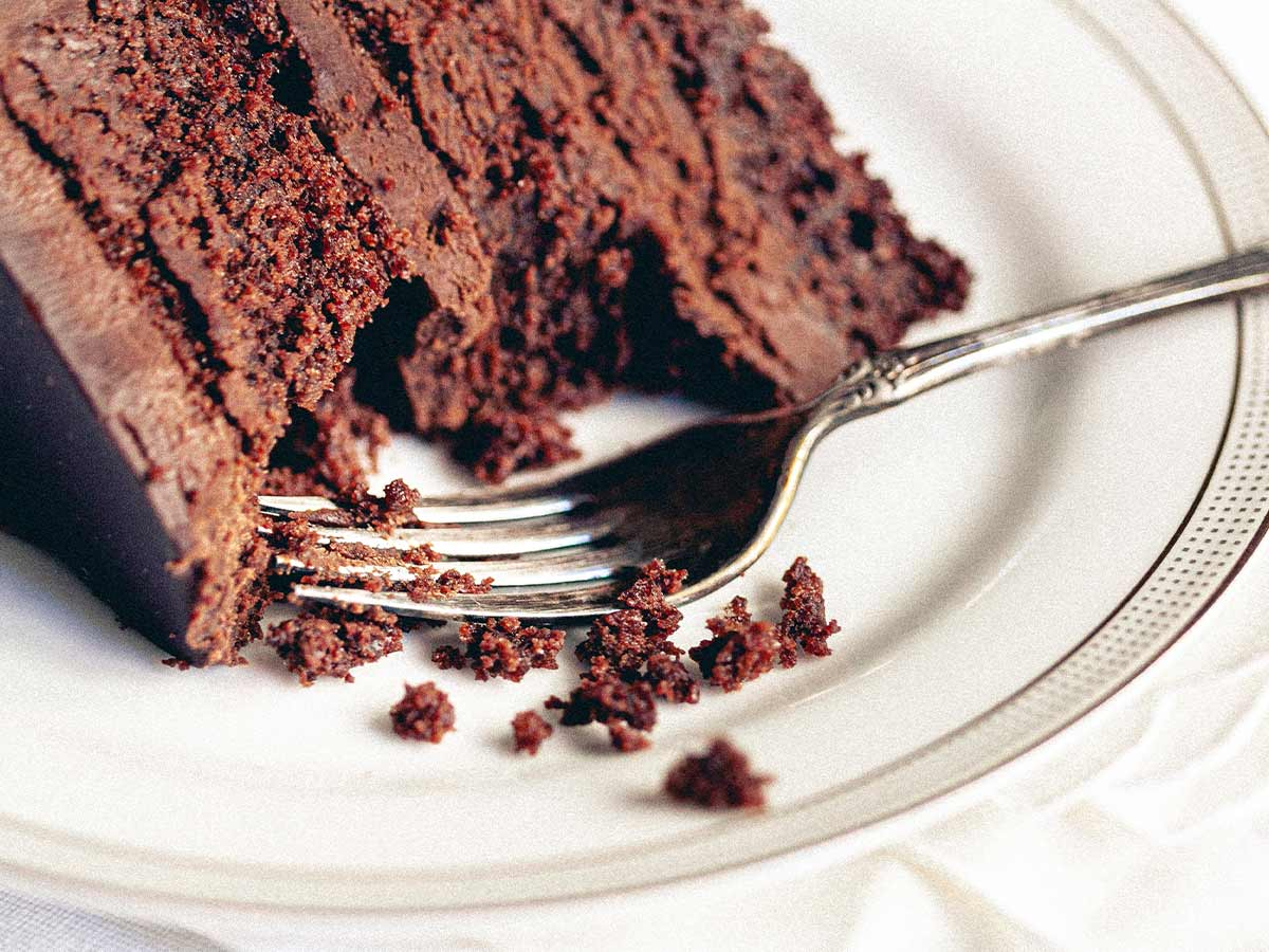 Slice of chocolate cake on a plate with a fork and a bite taken out of it.