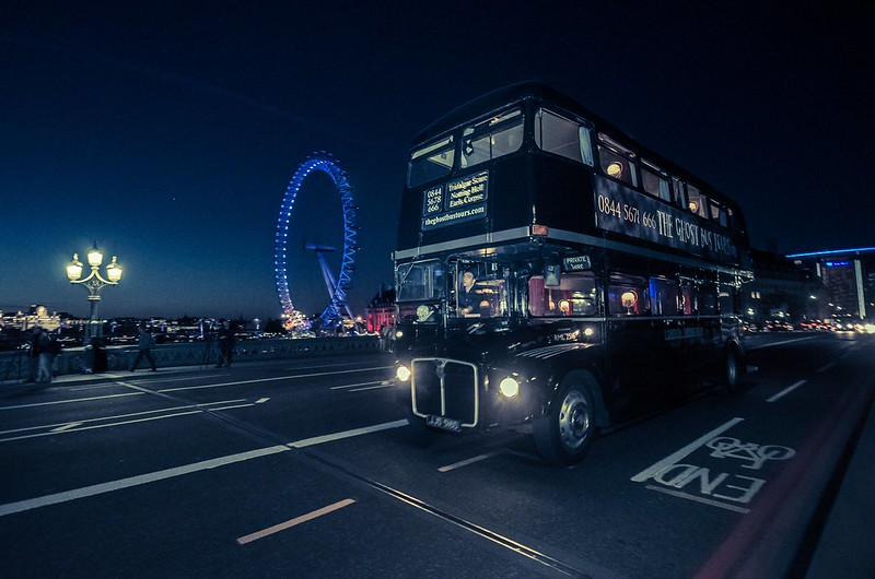 The Ghost Bus Tour Routemaster bus driving through London at night with the London Eye in the background.