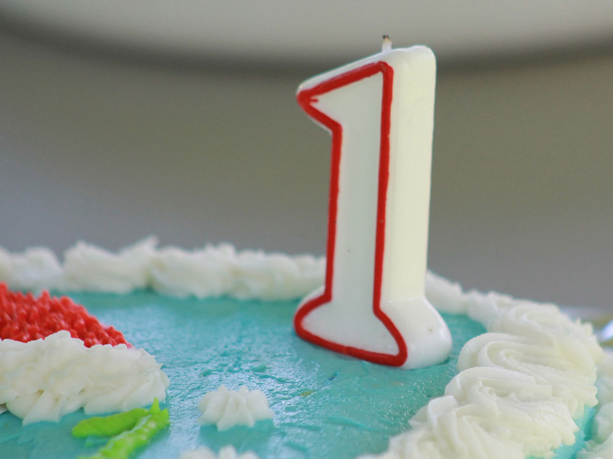 Number one candle on a blue birthday cake.