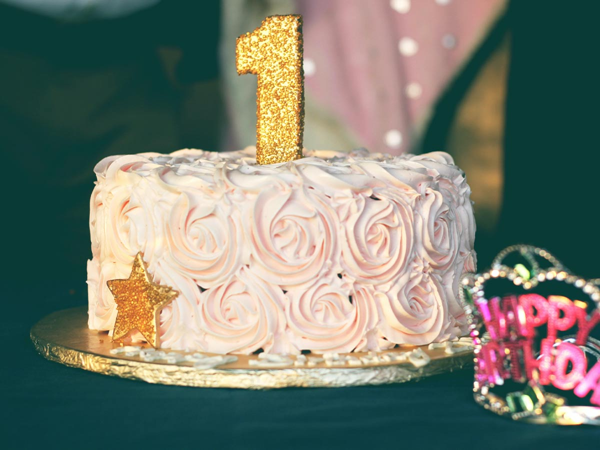 Birthday cake with light pink rose swirl icing and a gold number one candle on top.