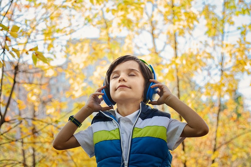 Boy wearing headphones while walking in the park.
