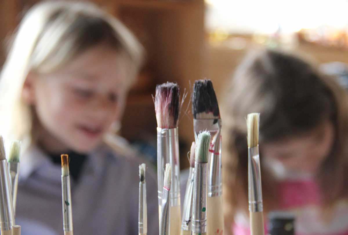 Close up of paintbrushes in the foreground, two girls making their own stamps behind.