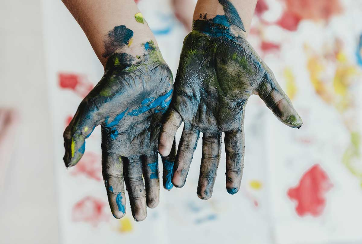 Hands, palms facing up, covered in blue and yellow paint from stamp making.