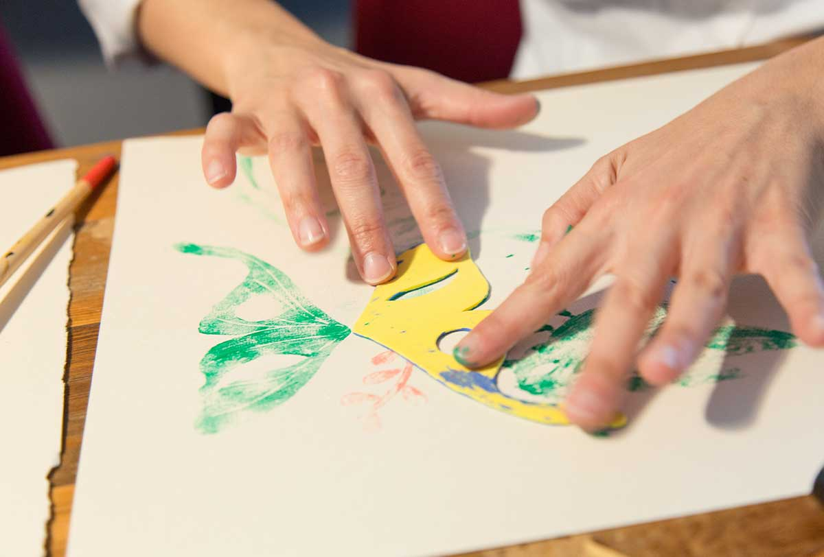Close up of a person's hands as they use a stamp to paint a green butterfly.