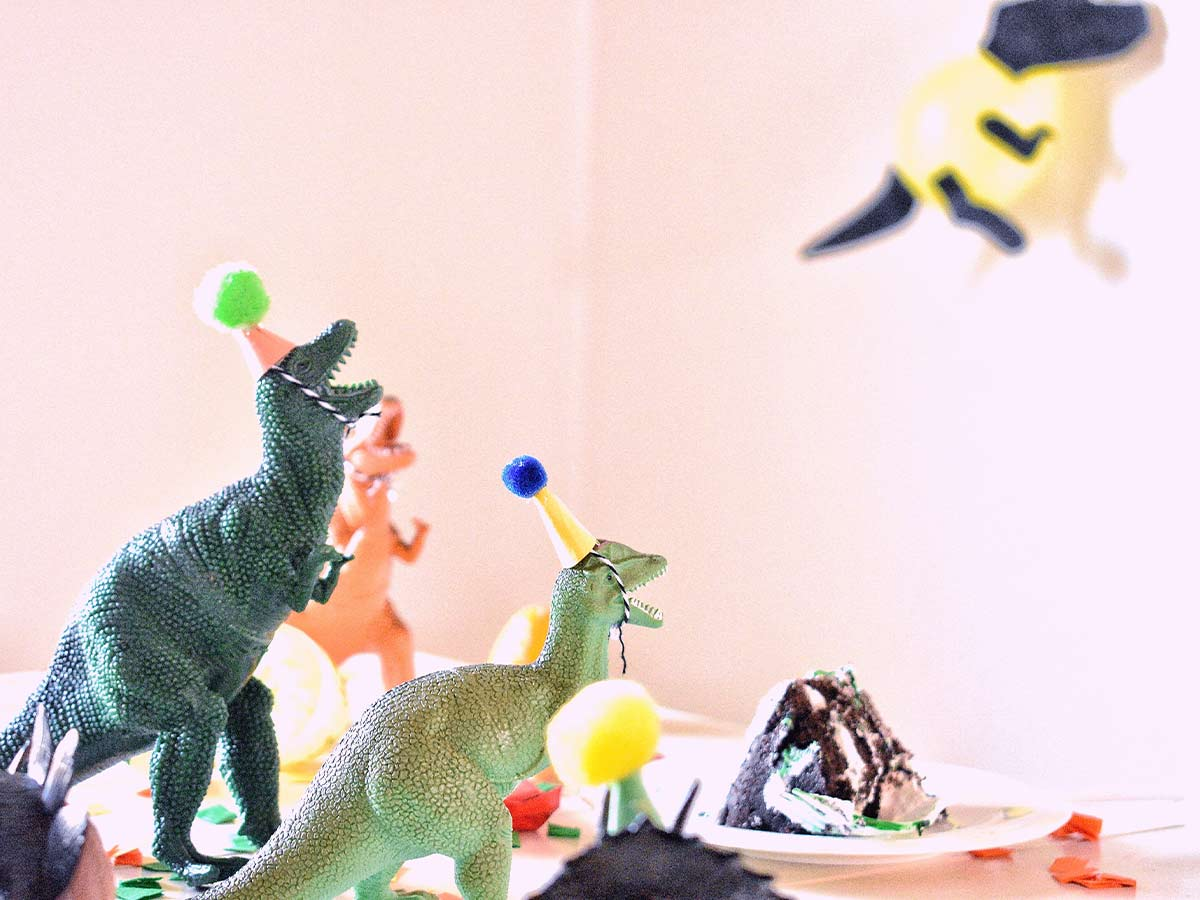 Toy dinosaurs wearing party hats on a table surrounding a piece of birthday cake.