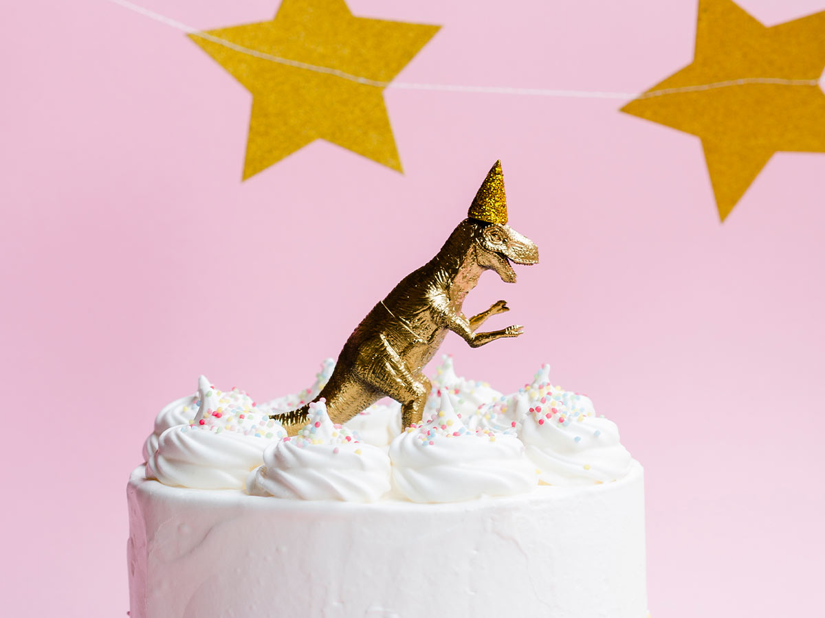 White cake with a gold dinosaur toy model on top.