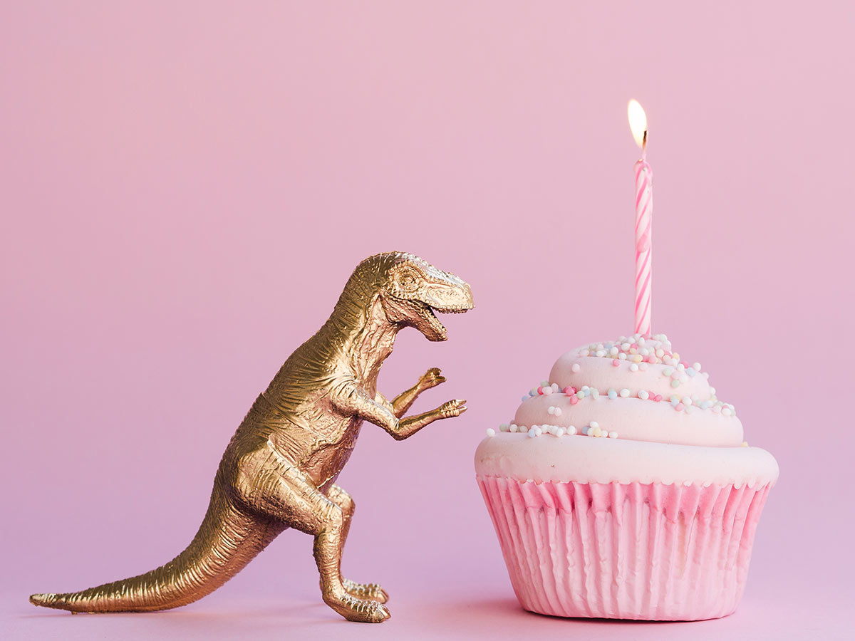 Gold dinosaur toy facing a pink cupcake with a lit candle in it.