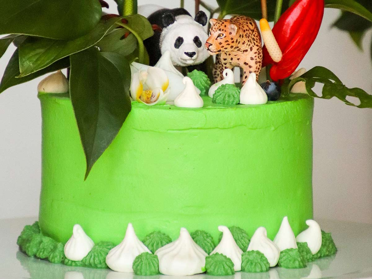 Bright green cake with jungle animal figures, including a panda and a tiger, on top.