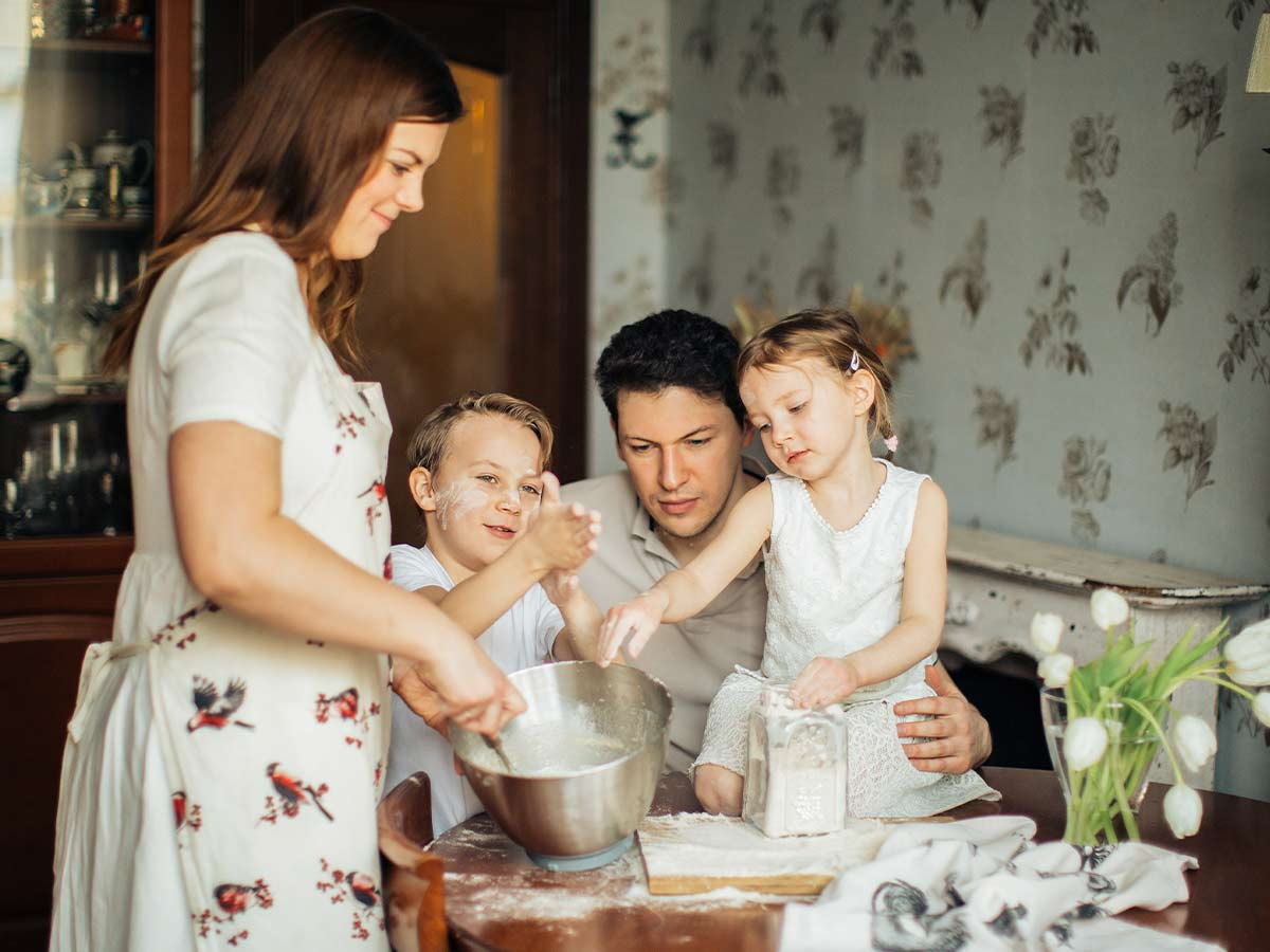 Family of four in the kitchen baking a panda cake together.