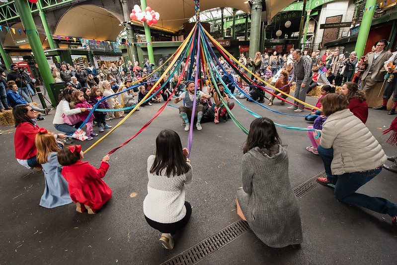 Families sat around colourful maypole as part of St George's Day Celebration.