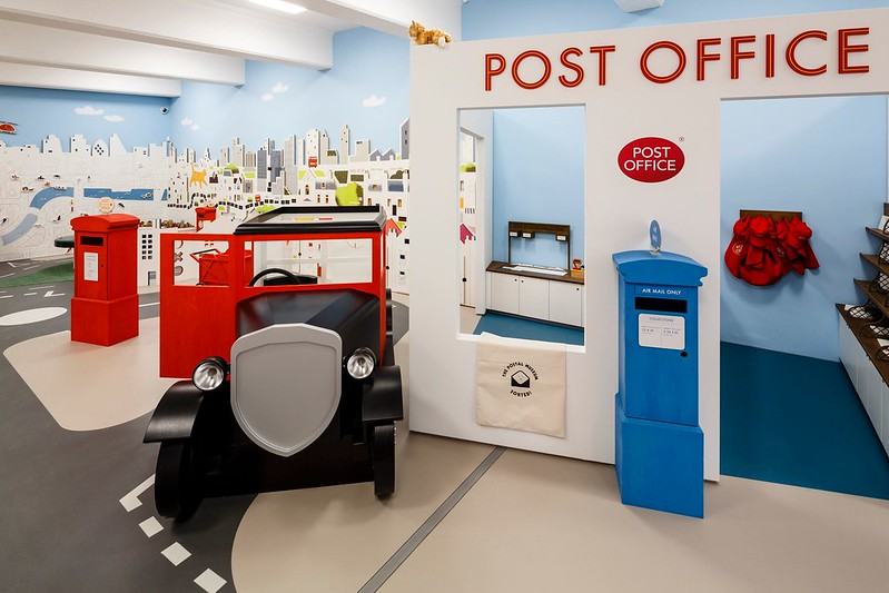 Life size model of postal office with post box and car.