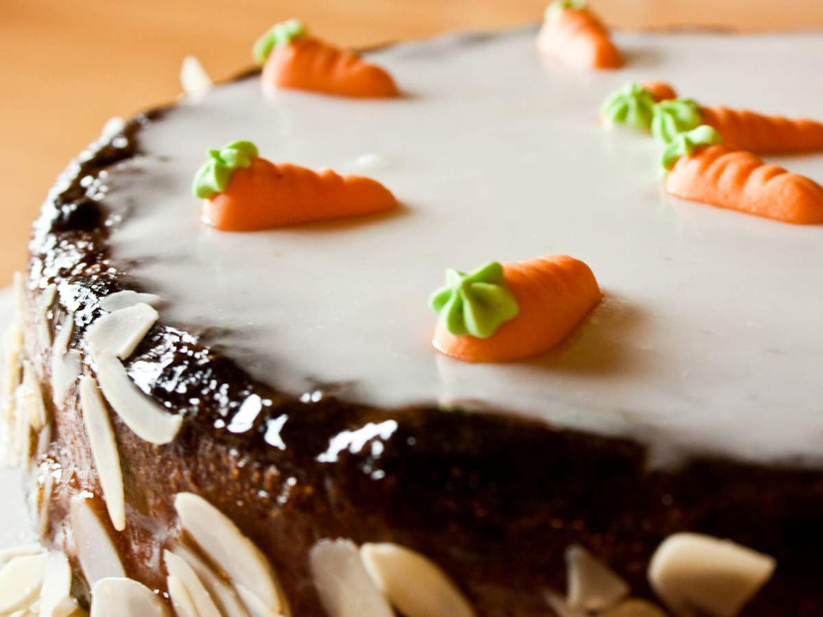 Close up of a cake with white icing and icing carrots on top.