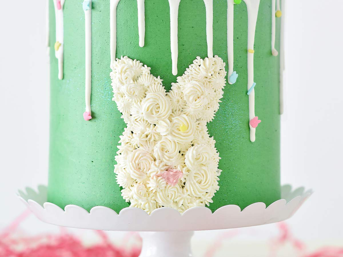 The side of a green birthday cake with white icing in the shape of a rabbit head.