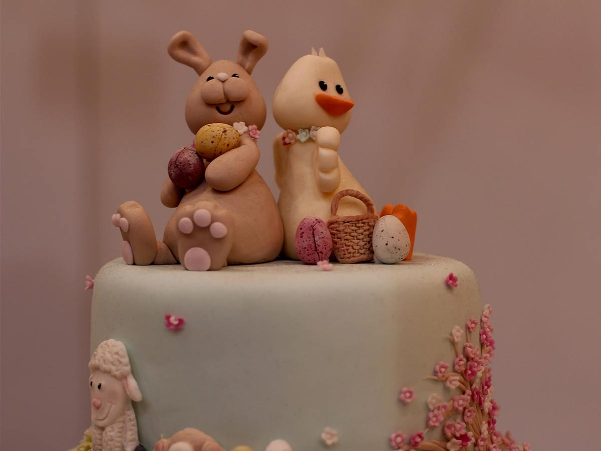 Easter cake with a fondant icing rabbit and chick sat on the top.