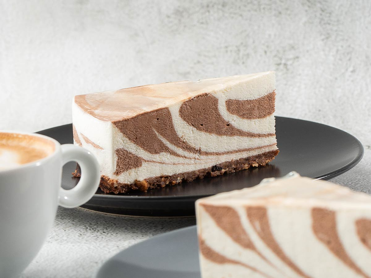 A slice of zebra cake on a plate and a mug of coffee.
