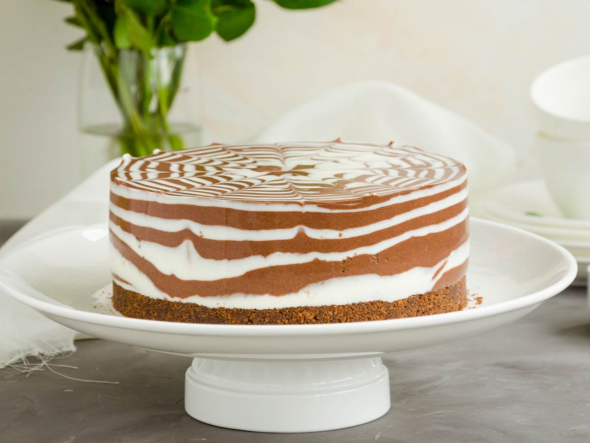 A whole zebra cake, the vanilla and chocolate swirled together, on a white plate.