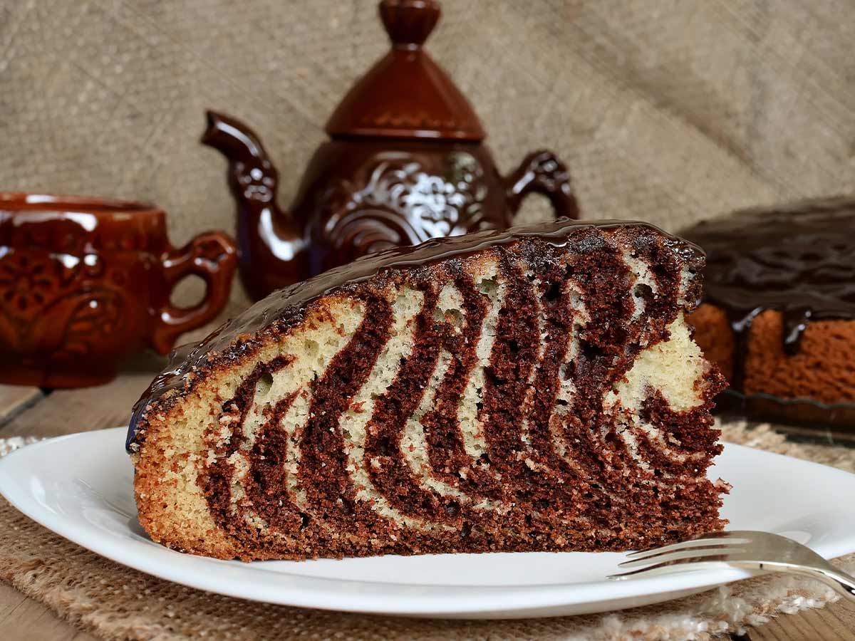 A slice of zebra cake with chocolate glaze.